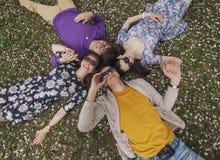 Amigos hermosos de la gente que mienten en la sonrisa de la hierba Foto de archivo libre de regalías