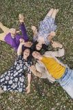 Amigos hermosos de la gente que mienten en la sonrisa de la hierba Imagenes de archivo