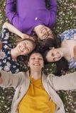 Amigos hermosos de la gente que mienten en la sonrisa de la hierba Foto de archivo