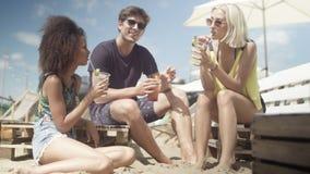 Amigos hermosos jovenes de la raza mixta que se sientan en sunbeds debajo del paraguas y que disfrutan de vacaciones Foto de archivo libre de regalías
