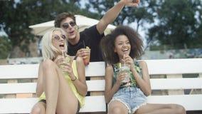 Amigos hermosos jovenes de la raza mixta que se sientan en sunbeds debajo del paraguas y que disfrutan de vacaciones Imagenes de archivo