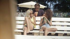 Amigos hermosos jovenes de la raza mixta que se sientan en sunbeds debajo del paraguas y que disfrutan de vacaciones Imagen de archivo