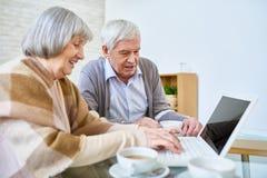 Amigos idosos com o portátil no lar de idosos fotografia de stock royalty free