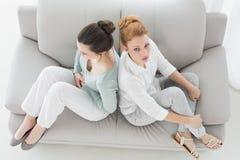 Amigos infelices que no hablan después de la discusión en el sofá Imagen de archivo