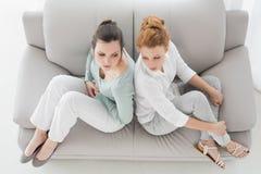 Amigos infelizes que não falam após o argumento no sofá Imagem de Stock