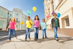 Amigos internacionais com caminhada colorida dos balões Imagem de Stock
