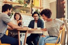 Amigos jovenes alegres que se divierten en un café Foto de archivo