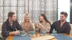 Amigos jovenes alegres que se sientan en la tabla con las tazas en balneario almacen de video