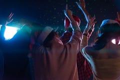 Amigos jovenes asiáticos del grupo que bailan junto el partido con el ligh del disco Foto de archivo