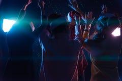 Amigos jovenes asiáticos del grupo que bailan junto el partido con el ligh del disco Imagen de archivo libre de regalías