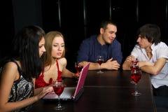 Amigos jovenes con la computadora portátil en una barra. Imagen de archivo