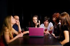 Amigos jovenes con la computadora portátil en una barra. Imagenes de archivo
