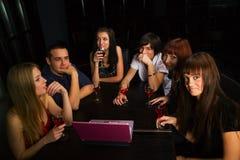 Amigos jovenes con la computadora portátil en una barra. Fotos de archivo