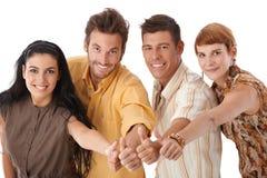 Amigos jovenes con los pulgares para arriba Imagen de archivo libre de regalías