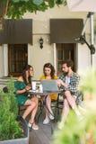 Amigos jovenes con smartphones y ordenador portátil en café con café Fotografía de archivo libre de regalías