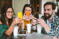 Amigos jovenes con smartphones y ordenador portátil en café con café Foto de archivo libre de regalías