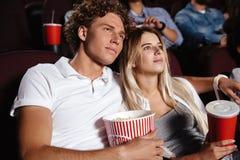 Amigos jovenes concentrados que aman los pares que se sientan en cine Imagen de archivo