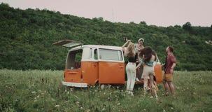 Amigos jovenes de baile en la comida campestre, tomando selfies, y pasando un buen rato, detrás del soporte una furgoneta retra metrajes