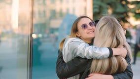 Amigos jovenes de la reuni?n de las muchachas que abrazan la calle de la ciudad almacen de video