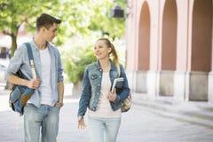 Amigos jovenes de la universidad que hablan mientras que camina en el campus Foto de archivo libre de regalías