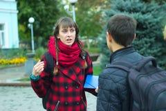 Amigos jovenes del estudiante que hablan en la universidad Imagen de archivo