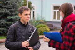 Amigos jovenes del estudiante que hablan en la universidad Fotografía de archivo