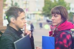 Amigos jovenes del estudiante que hablan en la universidad Fotos de archivo