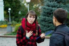 Amigos jovenes del estudiante que hablan en la universidad Intento de la muchacha para probar algo que señala el finger Foto de archivo