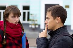 Amigos jovenes del estudiante que hablan en la universidad Intento de la muchacha para probar algo que señala el finger Fotografía de archivo