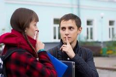 Amigos jovenes del estudiante que hablan en la universidad Intento del muchacho para probar algo que señala el finger Foto de archivo libre de regalías