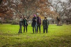 Amigos jovenes del tiro lleno que caminan alrededor del parque Foto de archivo libre de regalías