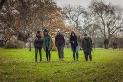 Amigos jovenes del tiro lleno que caminan alrededor del parque Fotos de archivo