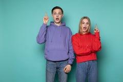Amigos jovenes emocionales de los pares que sorprenden en la ropa casual que presenta con la boca abierta que destacan con los fi fotografía de archivo libre de regalías
