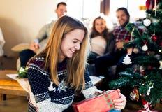 Amigos jovenes en el árbol de navidad adornado que celebran la Navidad Foto de archivo libre de regalías