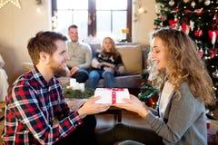 Amigos jovenes en el árbol de navidad adornado que celebran la Navidad Imágenes de archivo libres de regalías