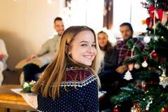 Amigos jovenes en el árbol de navidad adornado que celebran la Navidad Imagen de archivo libre de regalías