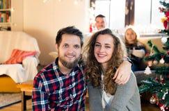 Amigos jovenes en el árbol de navidad adornado que celebran la Navidad Fotos de archivo libres de regalías