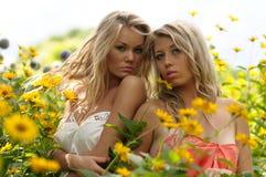 Amigos jovenes en flores amarillas del resorte Fotos de archivo