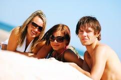 Amigos jovenes en la playa del verano Imagenes de archivo