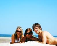 Amigos jovenes en la playa del verano Imágenes de archivo libres de regalías