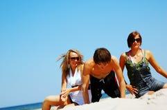 Amigos jovenes en la playa del verano Fotos de archivo