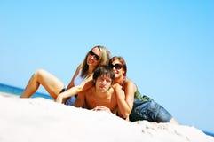 Amigos jovenes en la playa del verano Foto de archivo libre de regalías