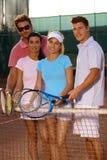 Amigos jovenes en la sonrisa del campo de tenis Imágenes de archivo libres de regalías
