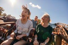 Amigos jovenes en paseo de la montaña rusa que emociona Foto de archivo libre de regalías