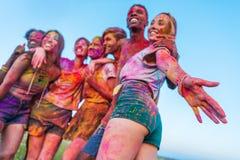 Amigos jovenes felices con la pintura colorida en la ropa que se une en el festival del holi Fotografía de archivo