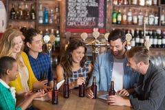 Amigos jovenes felices con las botellas de cerveza que se colocan alrededor de la tabla Fotos de archivo