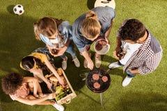 Amigos jovenes felices que asan a la parrilla las hamburguesas y que beben la cerveza en la comida campestre Imagen de archivo