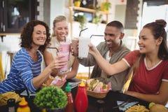 Amigos jovenes felices que aumentan bebidas mientras que se sienta en la cafetería Imagen de archivo libre de regalías