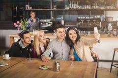 Amigos jovenes felices que beben el café en el café Imágenes de archivo libres de regalías