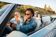 Amigos jovenes felices que conducen el coche en verano Fotos de archivo libres de regalías